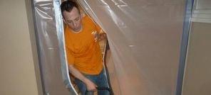 Water Damage Restoration Technician Using Air Mover Near Vapor Barrier
